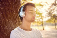 Young man with headphones listening to music outside - JHAF00042