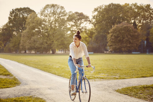 Young woman riding bike at a park - JHAF00048