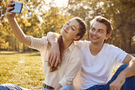 Young couple taking a selfie at a park - JHAF00069
