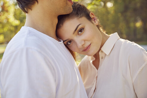 Portrait of young woman leaning against boyfriend's shoulder at a park - JHAF00072