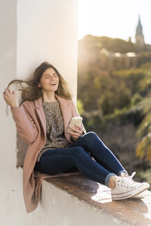 Laughing young woman sitting on a wall holding cell phone - AFVF02427