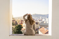 Rear view of a young woman sitting on a wall - AFVF02430