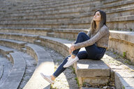 Young woman sitting on stairs outdoors looking around - AFVF02436