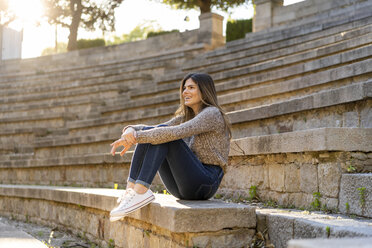 Happy young woman sitting on stairs outdoors - AFVF02439