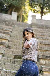 Portrait of a young woman on stairs reaching out her hand - AFVF02445