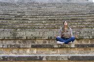 Young woman sitting outdoors on stairs doing yoga - AFVF02448