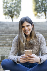 Portrait of a happy young woman holding cell phone - AFVF02451