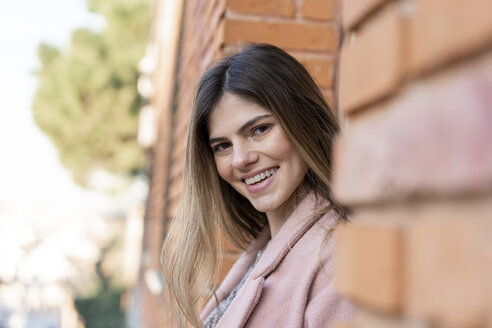 Portrait of a happy young woman at a brick building - AFVF02457