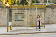 Young woman with cell phone waiting at bus stop - AFVF02466