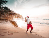 Thailand, man dressed up as Santa Claus posing on the beach at sunset - HMEF00211