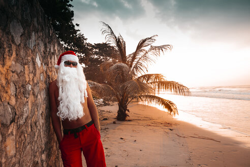 Thailand, man dressed up as Santa Claus leaning against wall on the beach at sunset - HMEF00214