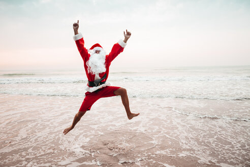 Thailand, man dressed up as Santa Claus jumping in the air at seashore - HMEF00217