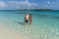 Caribbean, Bahamas, Exuma, Couple walking through the turquoise waters - RUNF01328