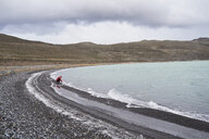 Chile, Patagonia, man touching cold water in Torres del Paine National Park - IGGF00769