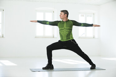 Man doing his fitness regime, practising yoga poses - MAEF12818