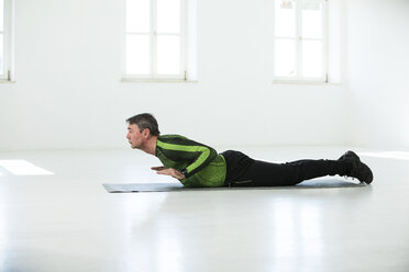 Man doing his fitness regime, practising yoga poses - MAEF12821