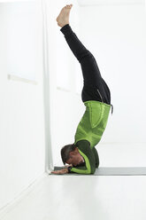 Man doing his fitness regime, practising forearmstand - MAEF12824