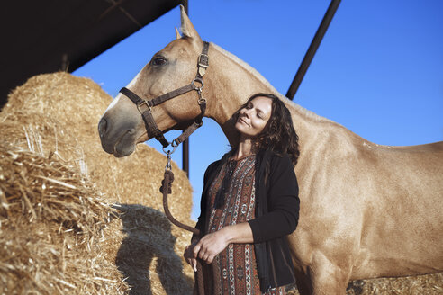 Pregnant woman with horse at hay barn - AZF00127