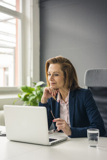 Businesswoman sitting in office, working on laptop - MOEF02050