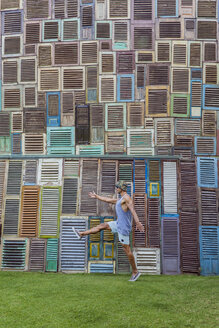 Indonesia, Bali, man walking at wall of wooden windows - KNTF02668