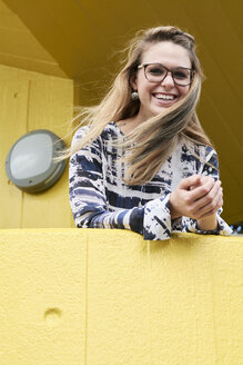 Portrait of laughing blond woman with blowing hair leaning on yellow balustrade - IGGF00797