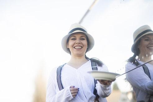 Junge Frau vor Foodtruck mit Strohhut und Hosenträger und Teller - SGF02242