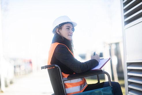 Junge Technikerin mit Helm im Rollstuhl arbeitend aussen - SGF02251