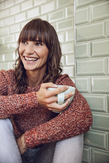 Happy woman sitting in kitchen, drinking tea - MCF00001