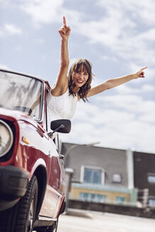 Cheering woman looking out of vintage car - MCF00016