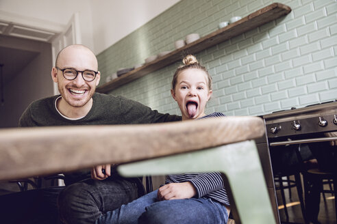 Father and daughter sitting in kitchen, girl pulling funny faces - MCF00019