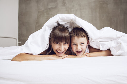 Mother and son cuddling under blanket, laughing - MCF00046