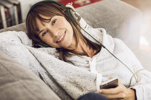 Woman lying couch, listening music with headphones - MCF00061