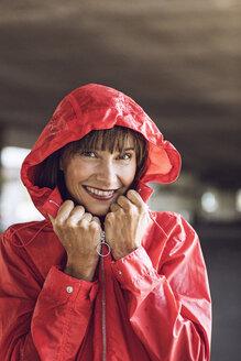Woman wearing red rain coat, portrait - MCF00079