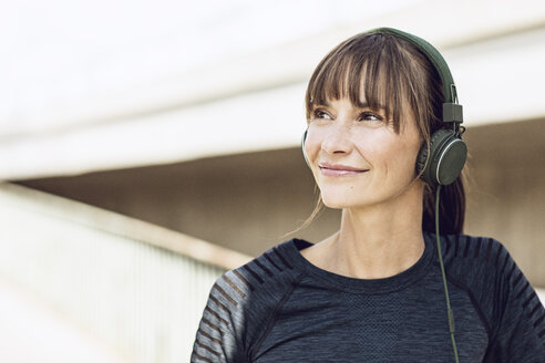 Sportive woman with headphones, doing her fitness training outdoors - MCF00085