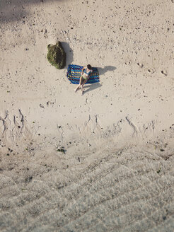 Woman relaxing on towel on the beach, top view - KNTF02670