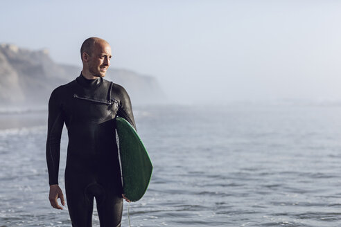 Surfer with surfboard wearing wetsuit looking at distance - MC00111