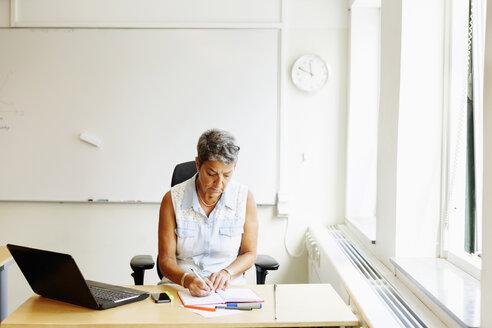 Mature female professor writing on book at desk in classroom - ASTF03956