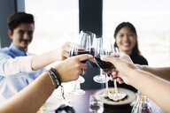 Cropped image of friends toasting with red wine in restaurant - ASTF04016