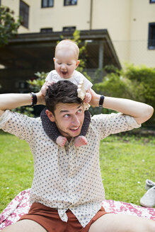 Playful baby girl sitting on father's shoulders at yard - ASTF04070