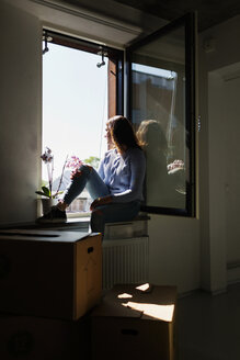 Thoughtful young woman sitting on window sill at new home - ASTF04091