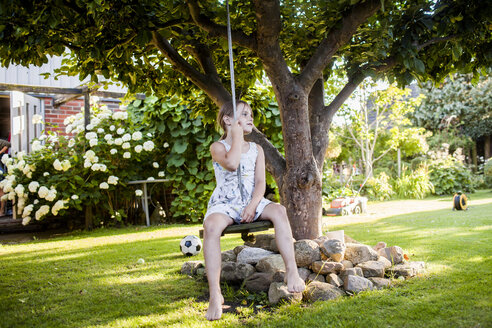 Thoughtful girl sitting on swing in garden - ASTF04196