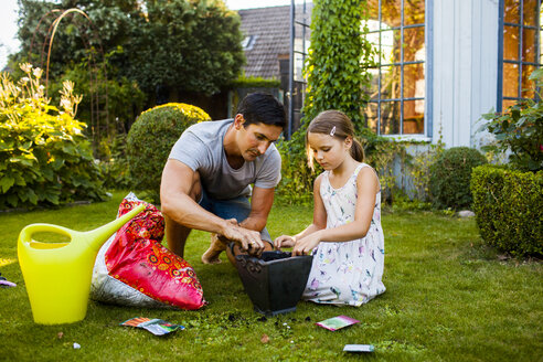 Father and daughter potting seeds in pot at backyard - ASTF04202