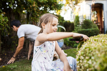 Girl pruning plant with father gardening in background - ASTF04205