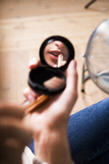 Reflection of fashion model applying lipstick in mirror at studio - ASTF04238