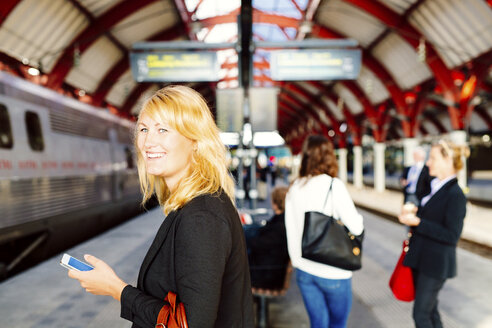 Side view of happy businesswoman holding smart phone while standing at railway station - ASTF04295