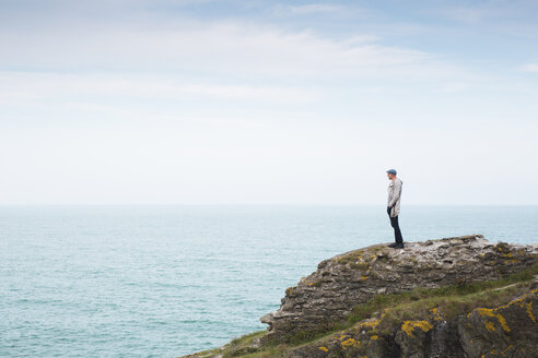 Side view of man standing on cliff by sea against sky - ASTF04334