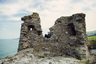 Man sitting on cliff against sky - ASTF04340
