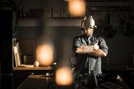 Man standing in kitchen, wearing colander as helmet - MJRF00030