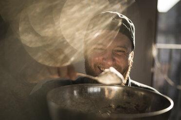 Laughing man holding bowl in kitchen, adding ingredients to his dough - MJRF00051