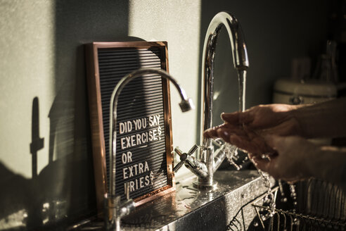 Board with funny text at the kitchen sink, where a man is washing his hands - MJRF00054